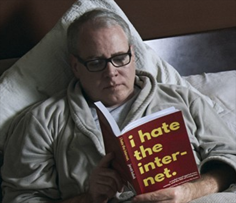 Bret Easton Ellis is in a bed. He is reading a book. That book is I HATE THE INTERENT. This photo is real.